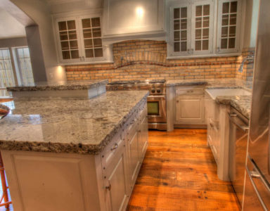 White cabinet kitchen, granite counters, brick backsplash.